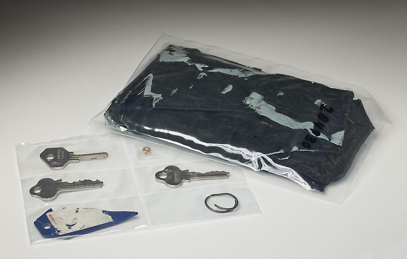 A dark blue leather wallet inside a plastic pouch, alongside another plastic pouch with six small compartments. These contain three silver keys, a remant of a blue plastic tag, a small metal ring and a metal earring fixture.