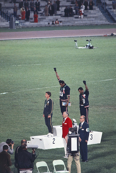 Side view of three men standing on an Olympic podium. Two have their gloved hands raised in a salute. - click to view larger image