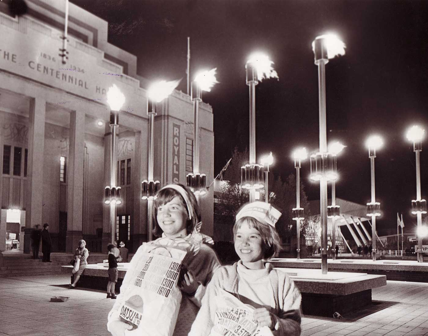 Black and white photo showing two girls posing with show bags outside the Centennial Hall at night. - click to view larger image