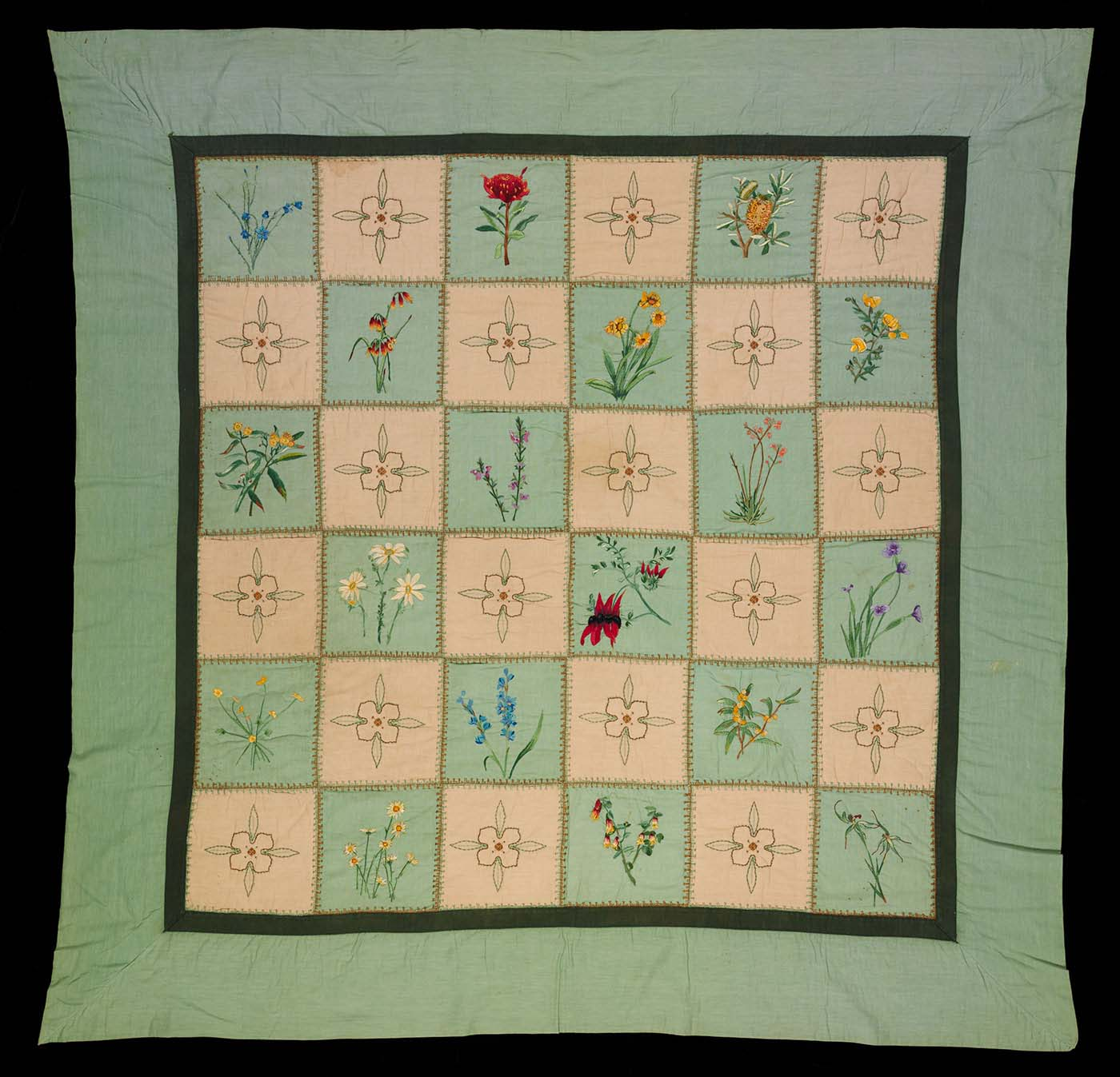 Fabric quilt with green and cream patchwork squares embroidered by hand with Australian wildflower designs, and a recurring passionfruit vine flower design.  - click to view larger image