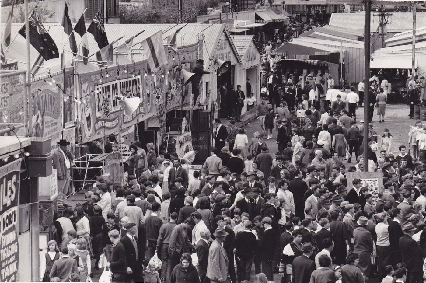 A crowd of people making their way through the sideshow alley at the Royal Adelaide Show. - click to view larger image