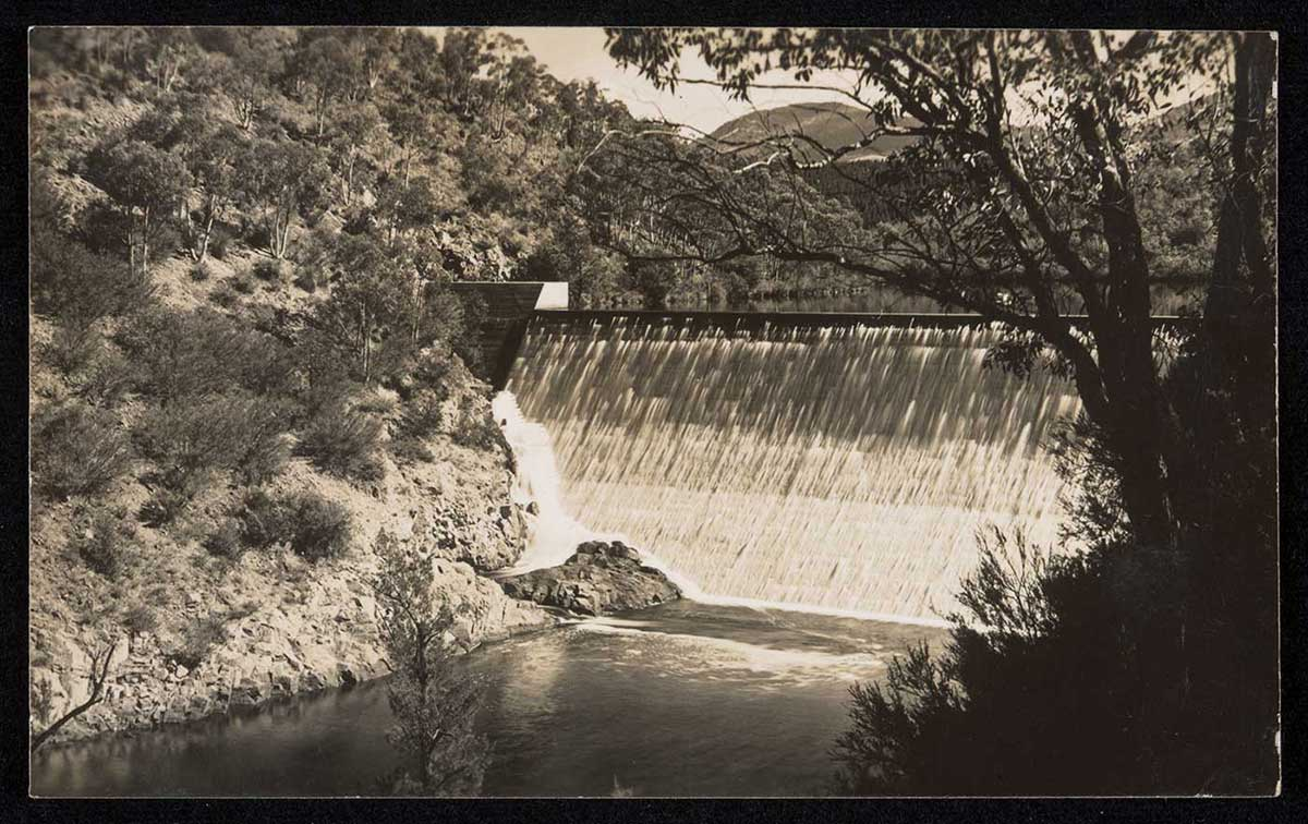 Black and white postcard showing a photograph of a concrete spillway, above a waterway. Gum trees line the steep bank on the left side. - click to view larger image
