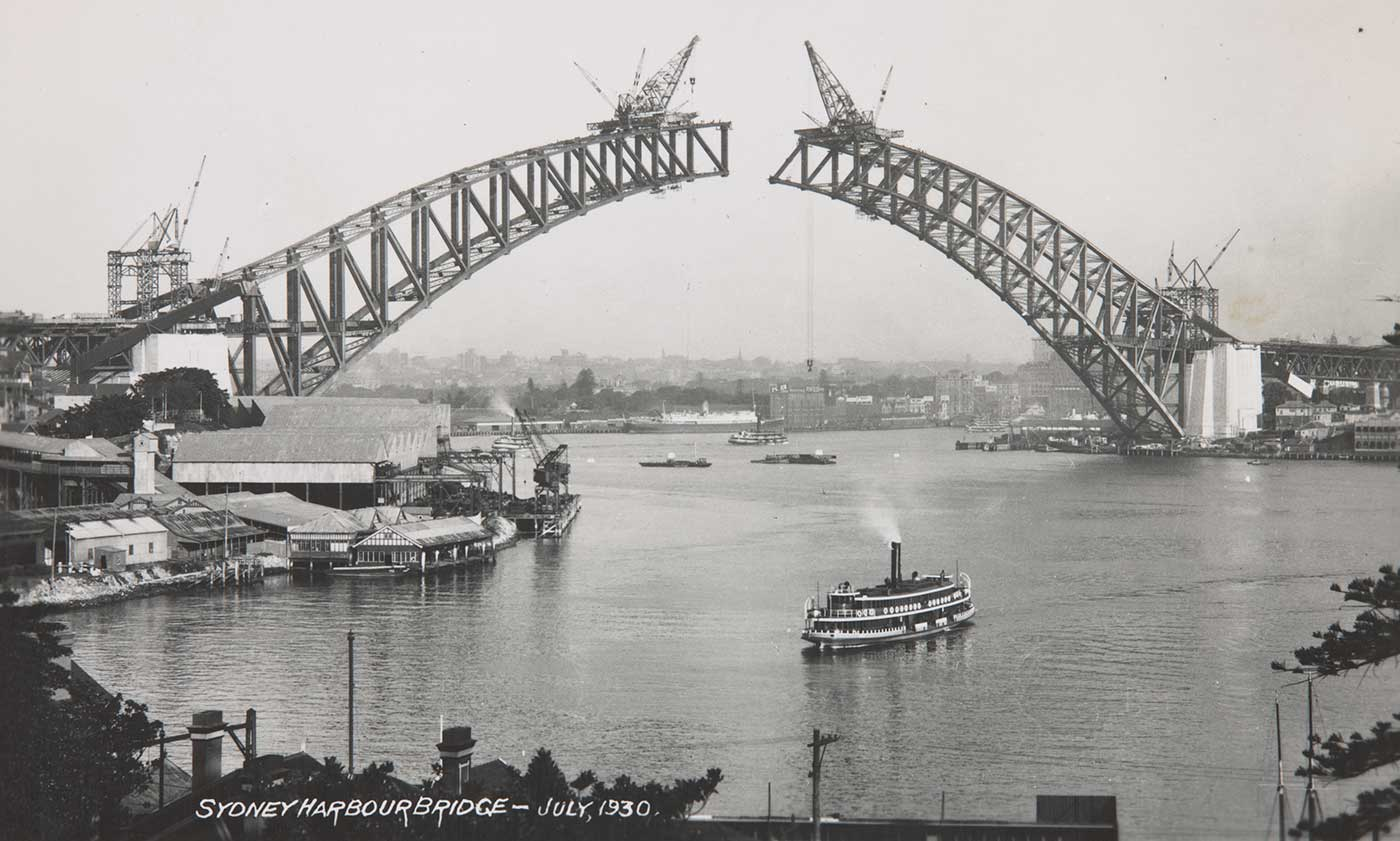 A photo of cranes of on each side of the arch of the Sydney Harbour Bridge before the sides converged in the centre. - click to view larger image