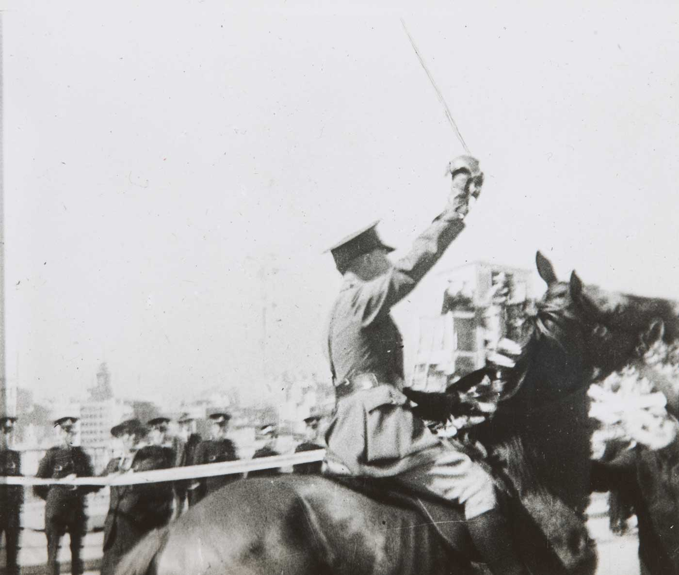 Black and white photo of a man on horseback with sword raised as he approaches a ribbon.  - click to view larger image