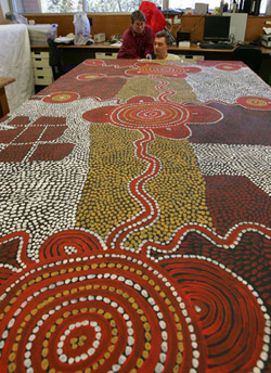Two conservators inspect far end of large Yumari 1976 dot painting by Uta Uta Tjangala.