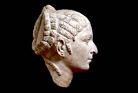 Side view of a sculpted head of a woman