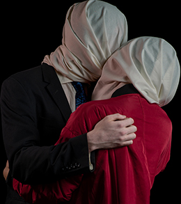 A man and woman in an embrace. They have their heads covered in light coloured fabric. The background is dark.