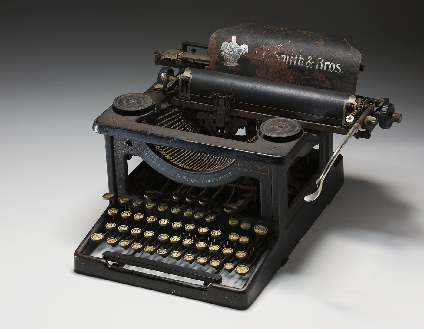 Black painted, steel framed, 'visible' typewriter with circular white pre-decimal keys. 'L.C. SMITH & BROS TYPEWRITER' is printed along an inverted arch across the front, which cradles the typeface heads. It is rusty and the ribbon is missing. - click to view larger image