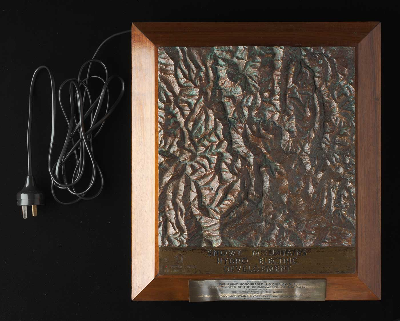 A bronze topographic plaque depicting the topography of the Snowy Mountains, mounted on a brown wooden plinth with the engraving 'SNOWY MOUNTAINS / HYDRO ELECTRIC / DEVELOPMENT' and a black electrical cord coming from the top left of the plaque - click to view larger image