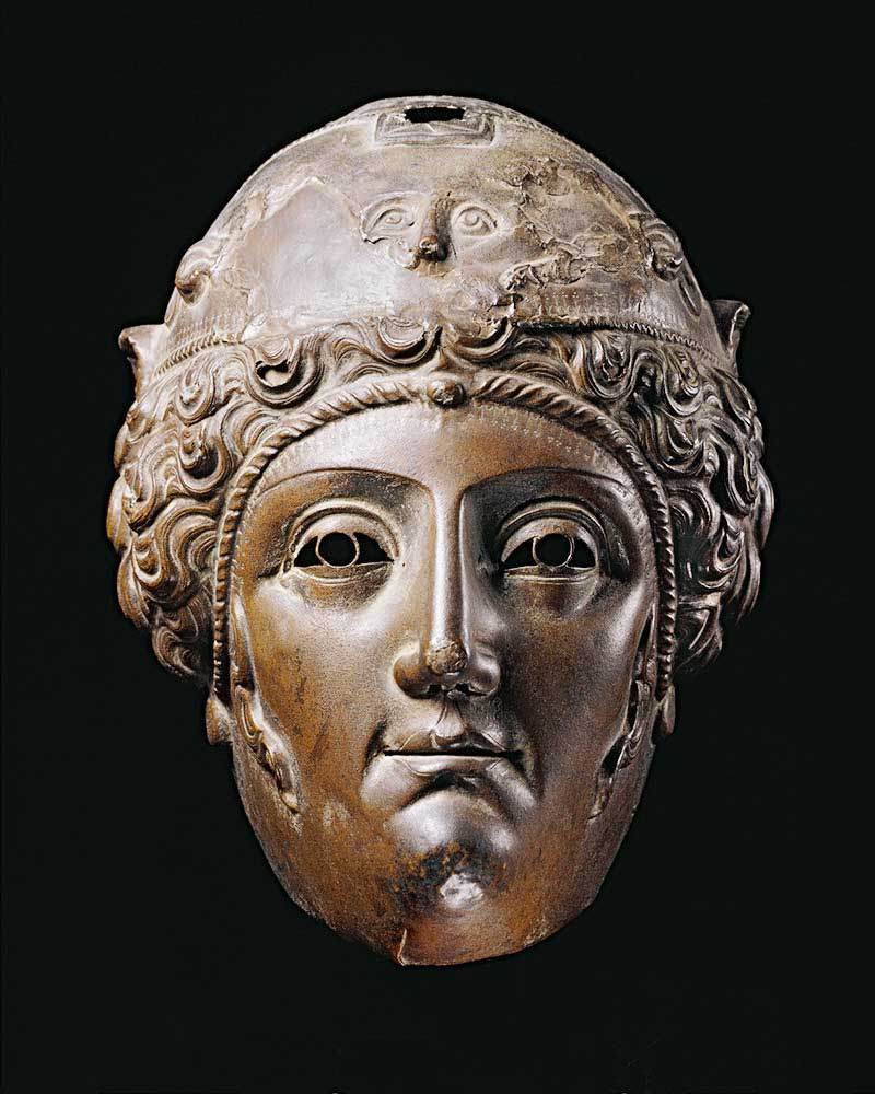 A bronze parade helmet with a woman's face. - click to view larger image