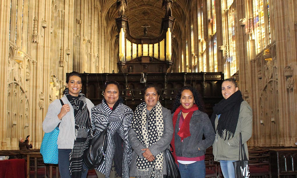 A group of five women, inside a cathedral-like building, pose for the camera  - click to view larger image