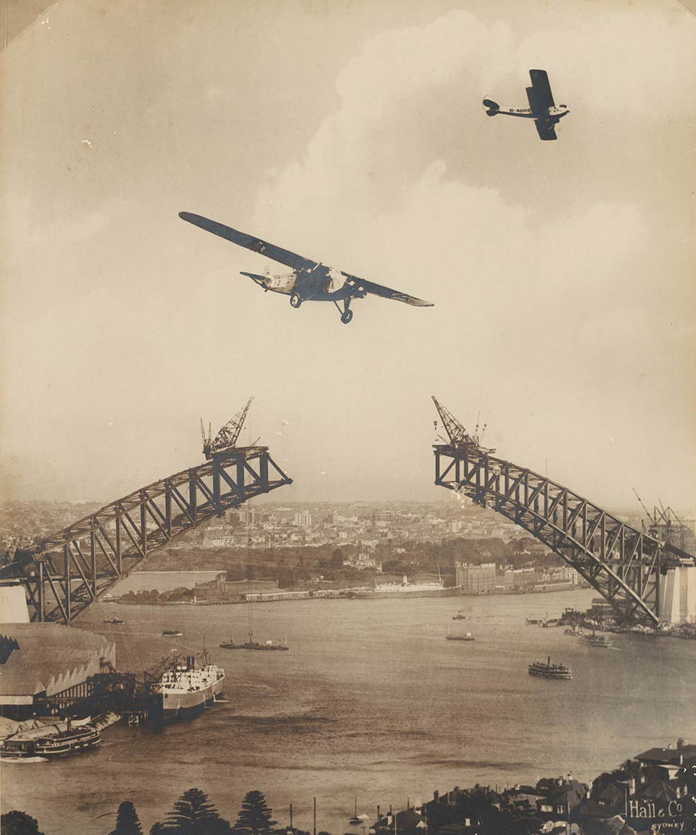 Black and white photograph showing two aeroplanes flying above Sydney Harbour and the the unjoined spans of Sydney Harbour Bridge. - click to view larger image