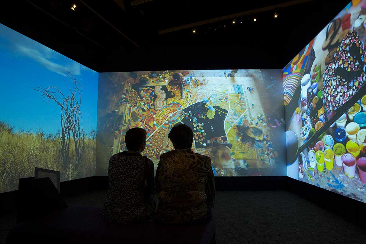 Silhouettes of two seated people watch a large and colourful video installation.