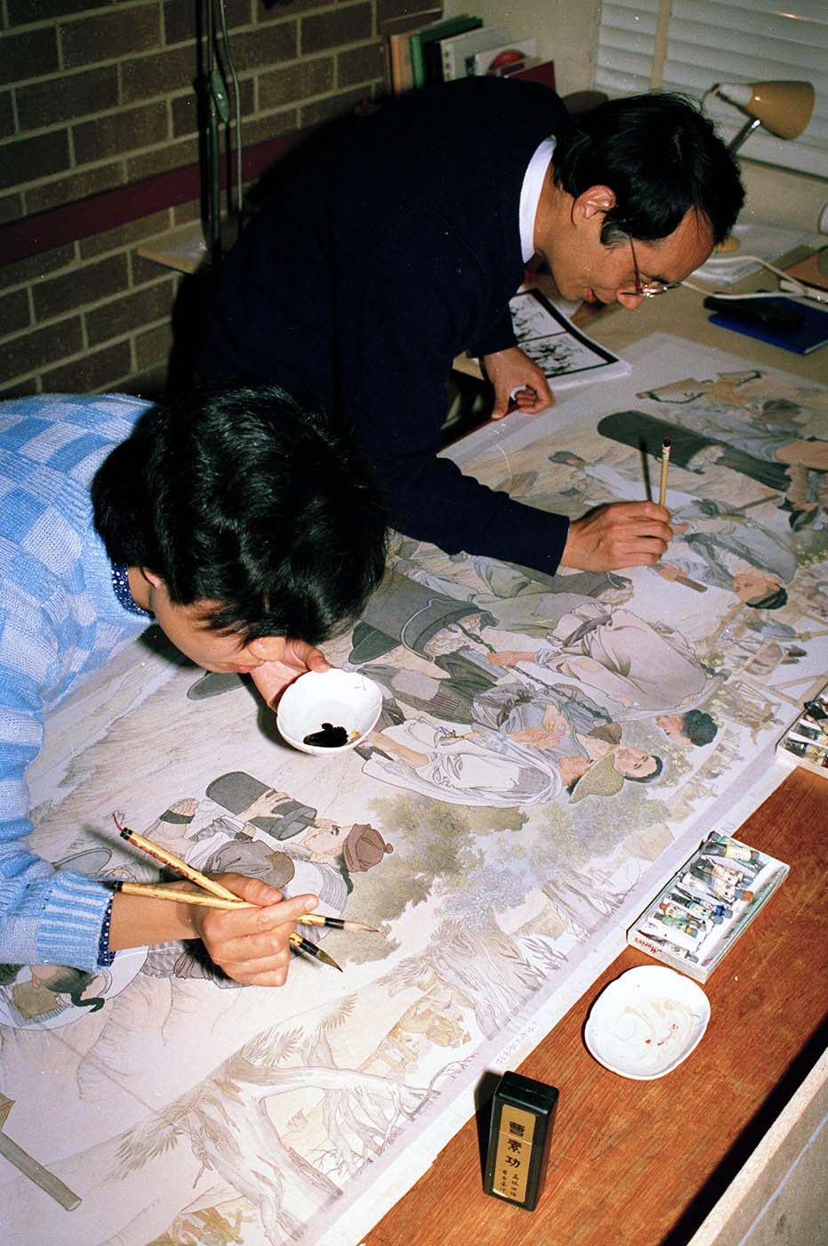 Artists Mo Xiangyi (right) and Wang Jingwen work on painting the Harvest of Endurance scroll. - click to view larger image
