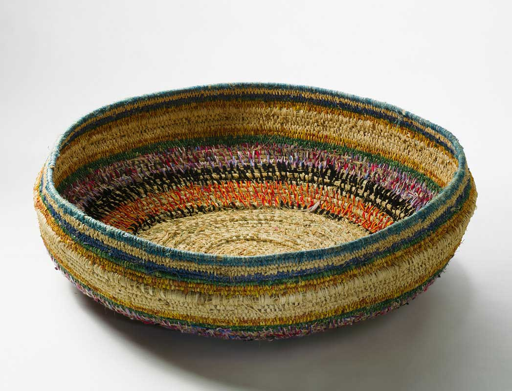 A large shallow basket made of bands of grasses which have been bound in plant material dyed in different colours and in strands of wool. - click to view larger image
