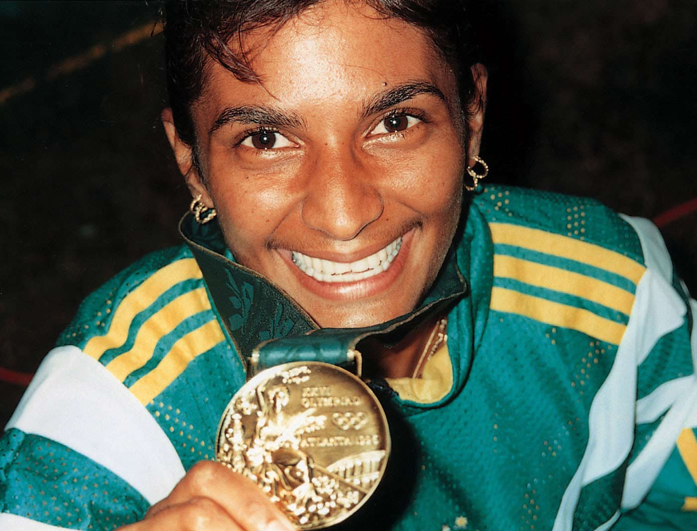 A smiling woman wearing green and gold tracksuits holds a gold medal.