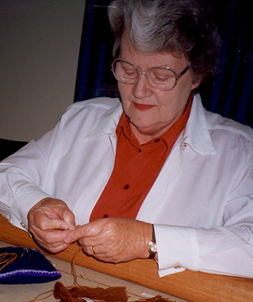 Embroiderer working on the Crimson Thread of Kinship embroidery.