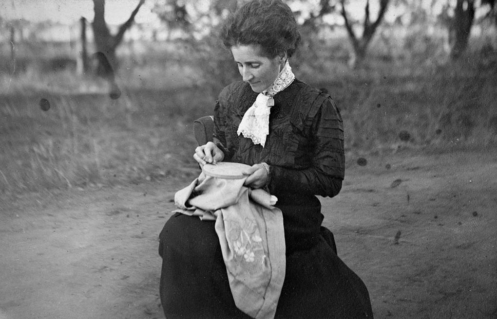 An old black and white photo of Clara Pitts sitting near the orchard embroidering a cloth held in an embroidery frame. - click to view larger image