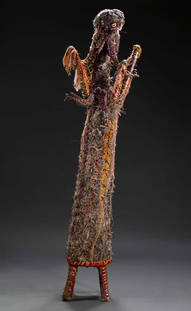 A tree sculpture with a human like figure seated at the top of it. The figure features, hair, a face, breasts, arms, fingers, legs and toes. The sculpture is made of various plant-based and synthetic materials. - click to view larger image