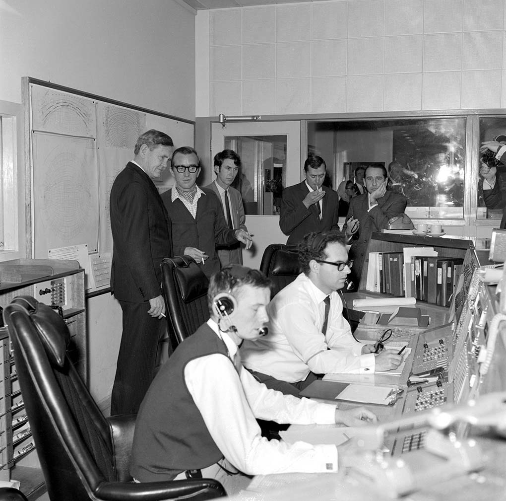 A black and white photo taken in 1969 featuring the then Prime Minister Gorton accompanied by several other men. They are watching on while two men, who are wearing headsets and seated, appear to be at a workstation. - click to view larger image