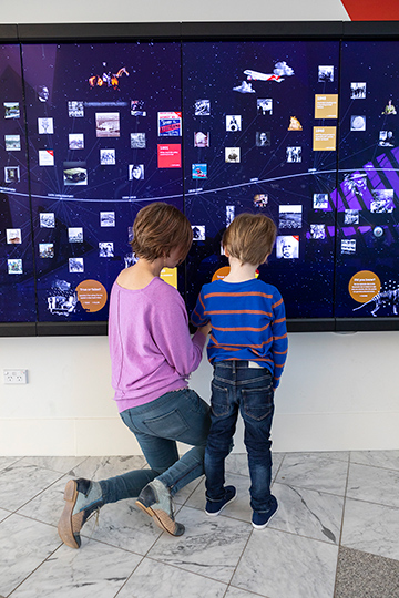 An adult and child are engaging with the Defining Moments Discovery Wall which is a large interactive screen mounted on a wall.