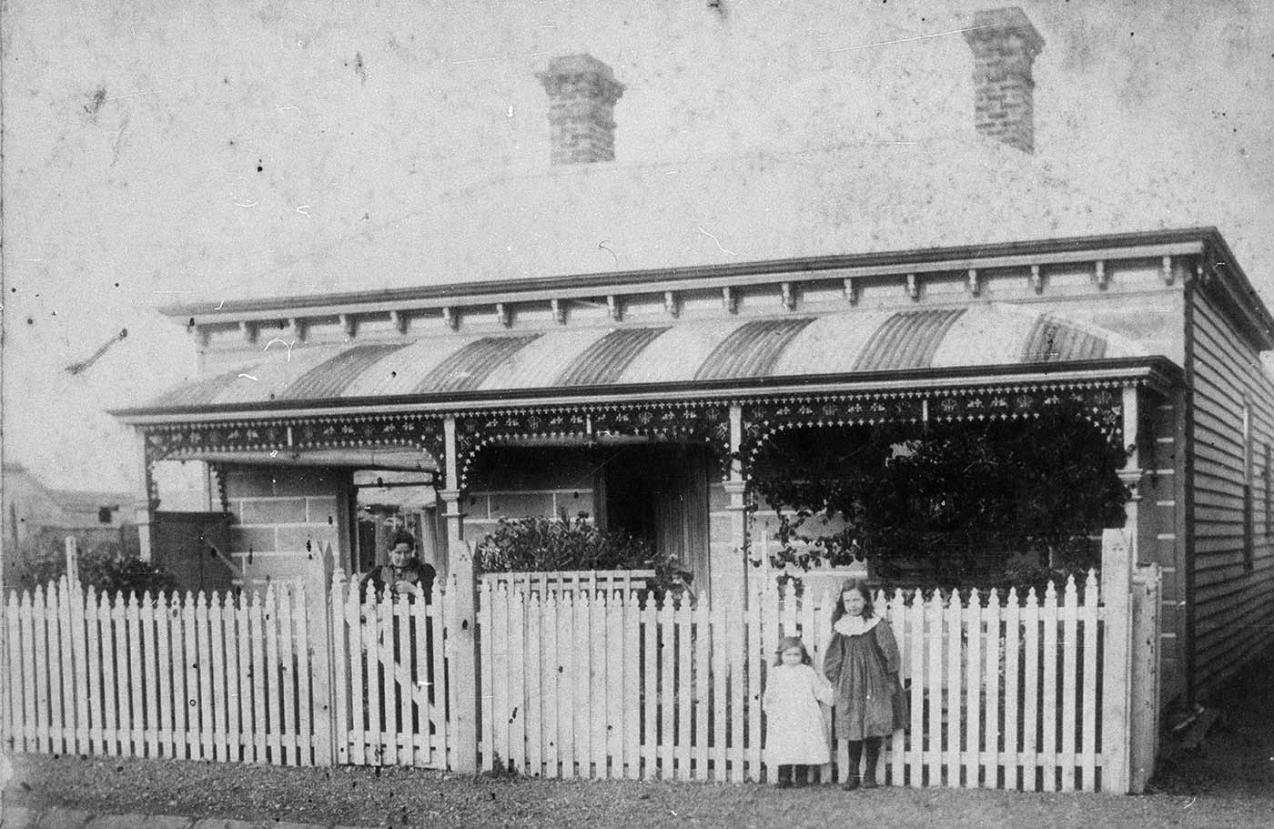 Black and white photo of an old style house with a woman and two children standing out the front.