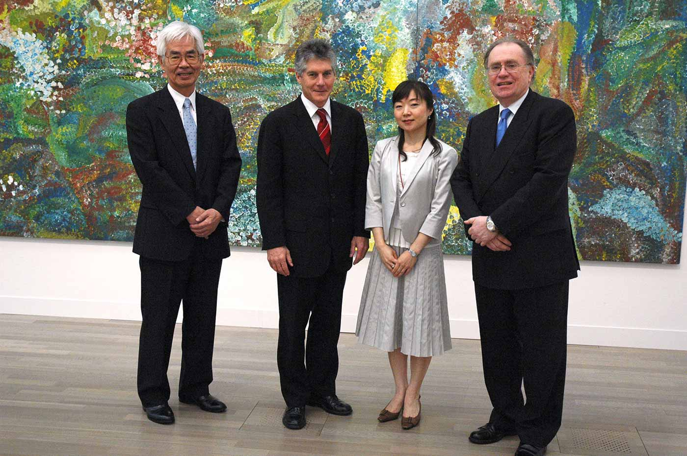 Three men and a woman standing in front of a large painting. - click to view larger image