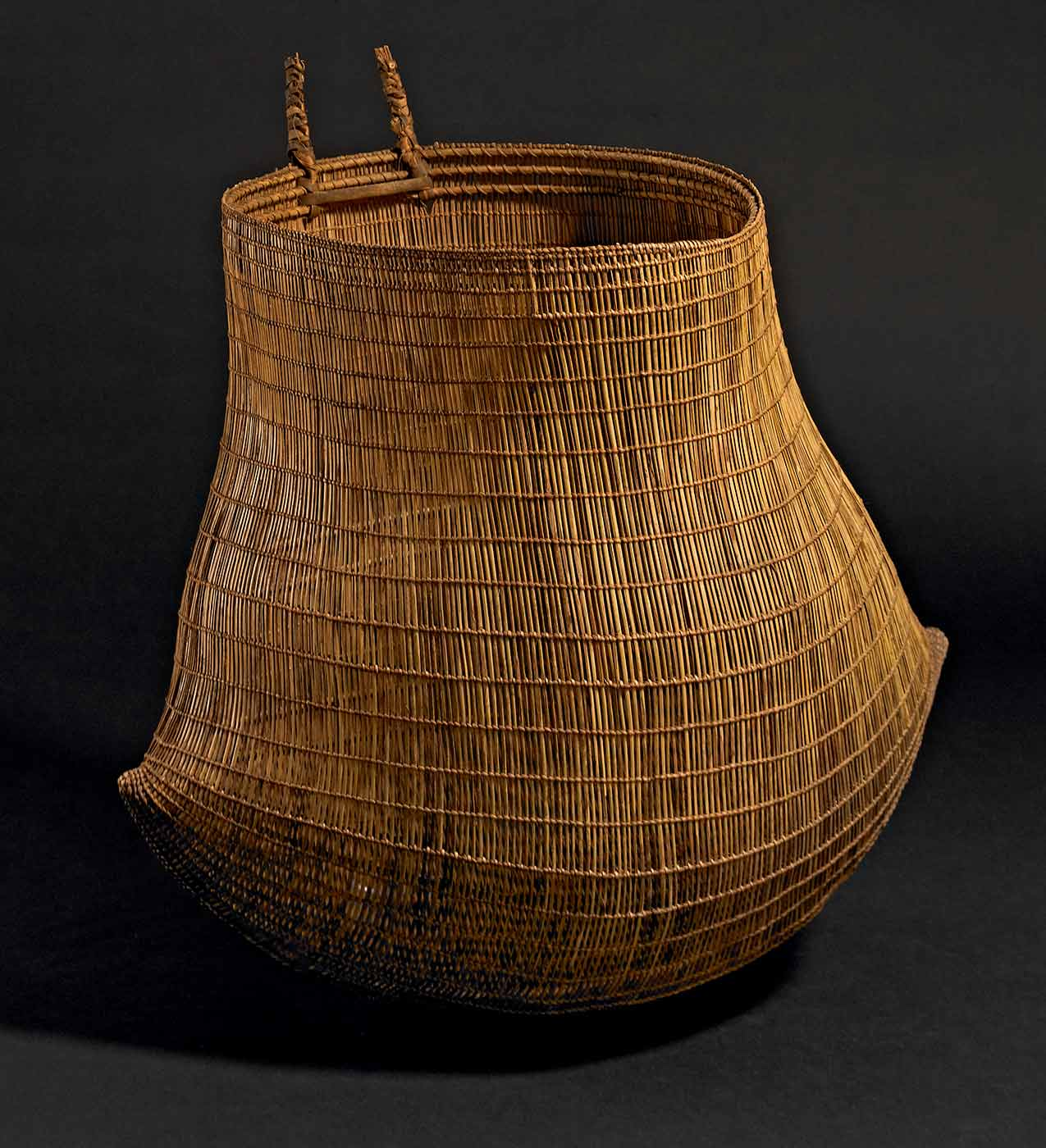 Roughly cylindrical basket woven from fibre, with two small handles extending from the opening. - click to view larger image