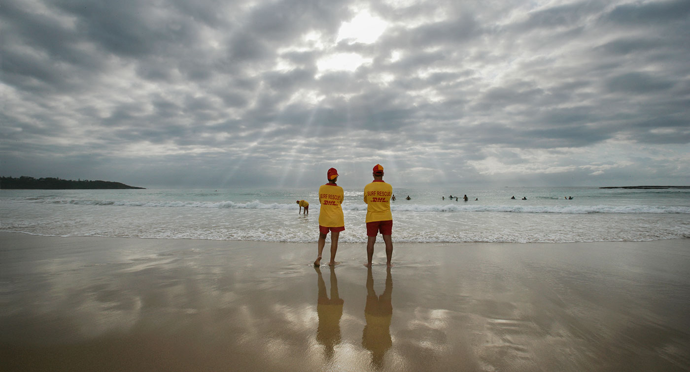 Two surf lifesavers standing on the beach looking towards the surf at Mollymook, New South Wales, 2006.