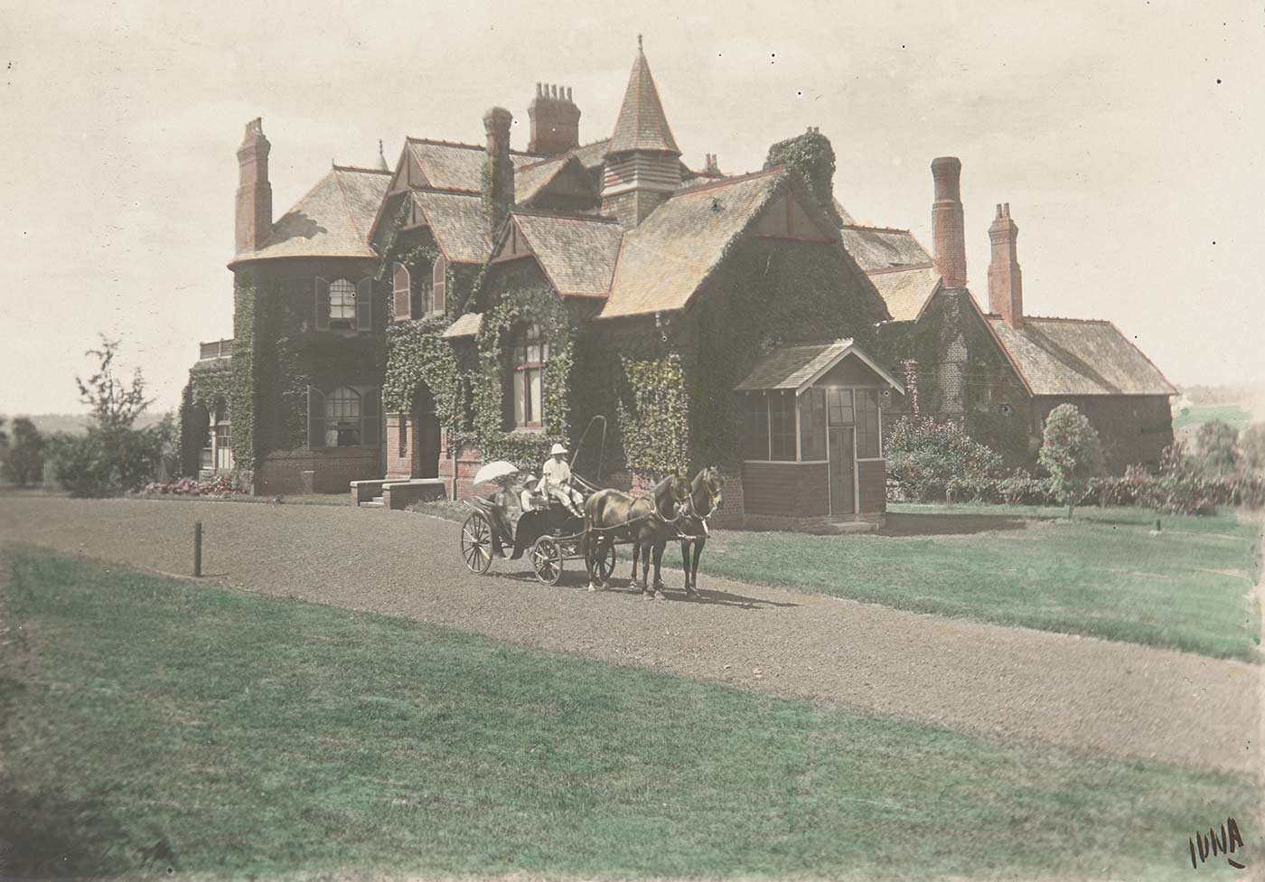 Carriage pulled by two horses on a path in front of a country house. - click to view larger image