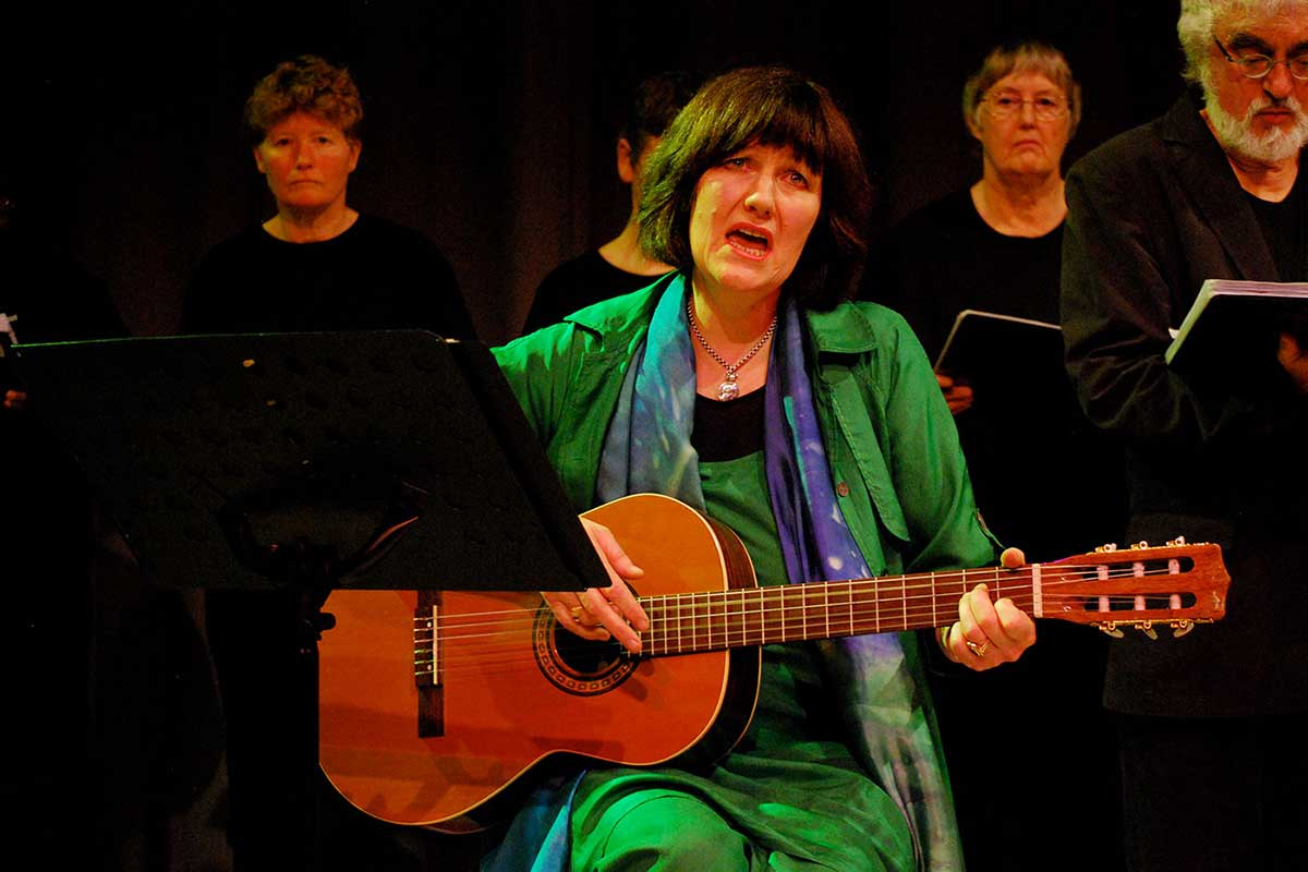 A woman is playing a guitar and singing while performing alongside a choir. - click to view larger image
