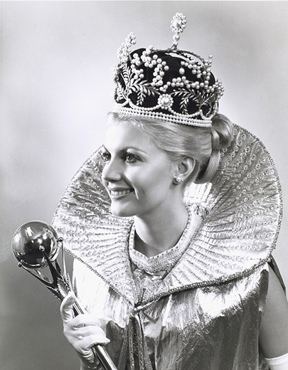 Miss Australia 1972, Gay Walker holding the sceptre wearing the crown, a gold frilled-collar, sleeveless cape and white gloves - click to view larger image