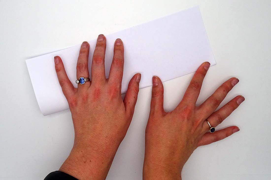 Two hands folding paper in half - click to view larger image