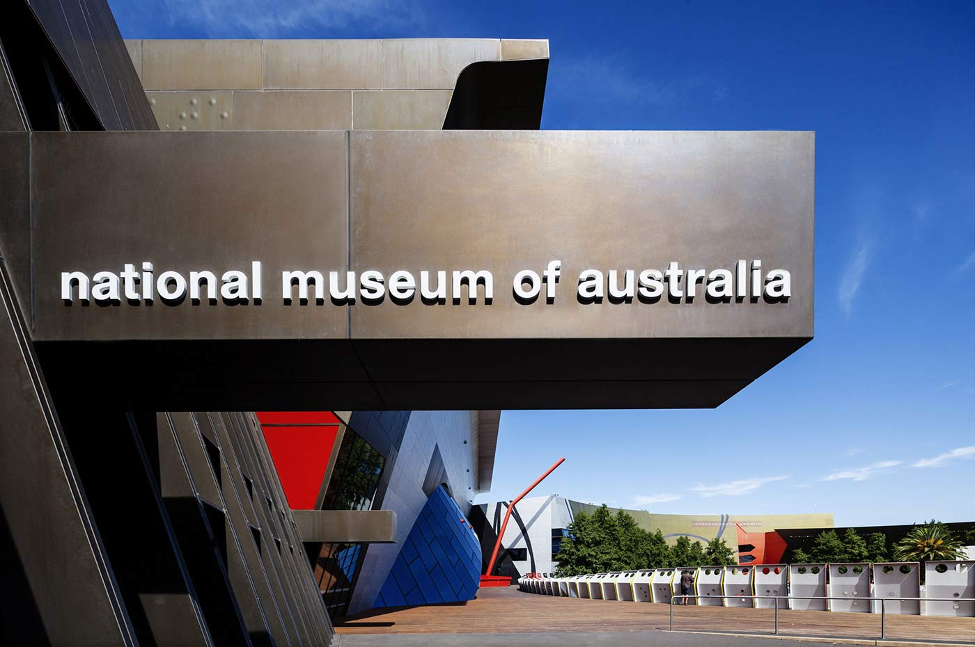 A view of the Museum's entrance with a large sign which spells 'National Museum of Australia' featuring above.