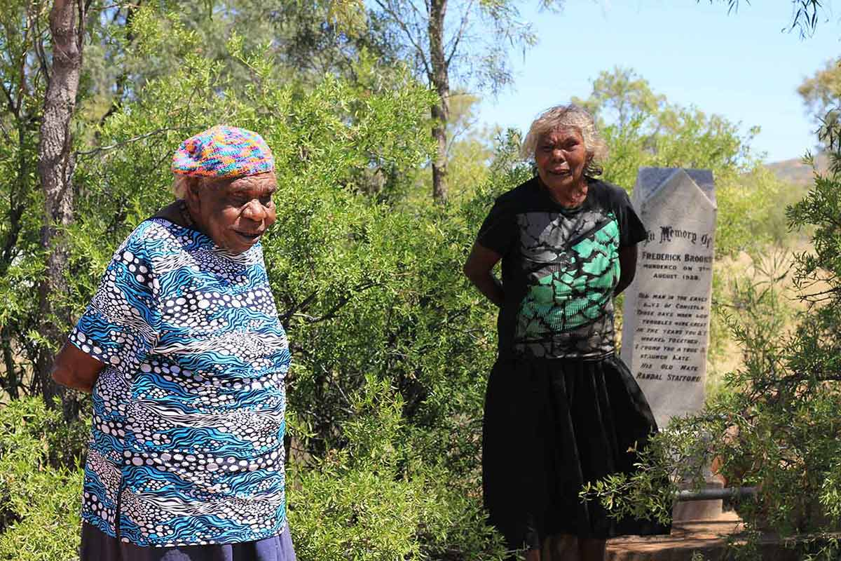 A photo of Liddy Napanangka Walker and Coral Napangardi Gallagher standing beside a headstone.