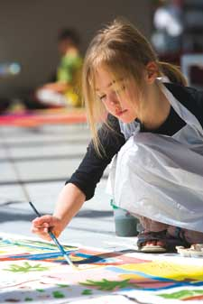 A young girl wearing a white apron kneels on the floor, leaning forward to add paint to a work on paper.
