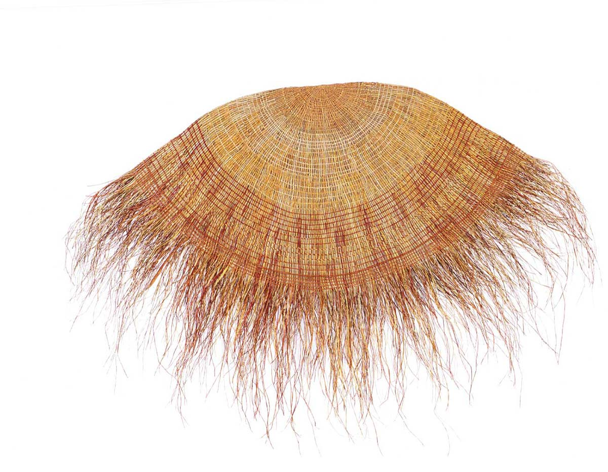 A mat made by an Indigenous Australian artist. The mat is round and is made from natural fibre. It is dyed in natural colours ie browns and ochres. Many loose strands hang from the edge of the mat.