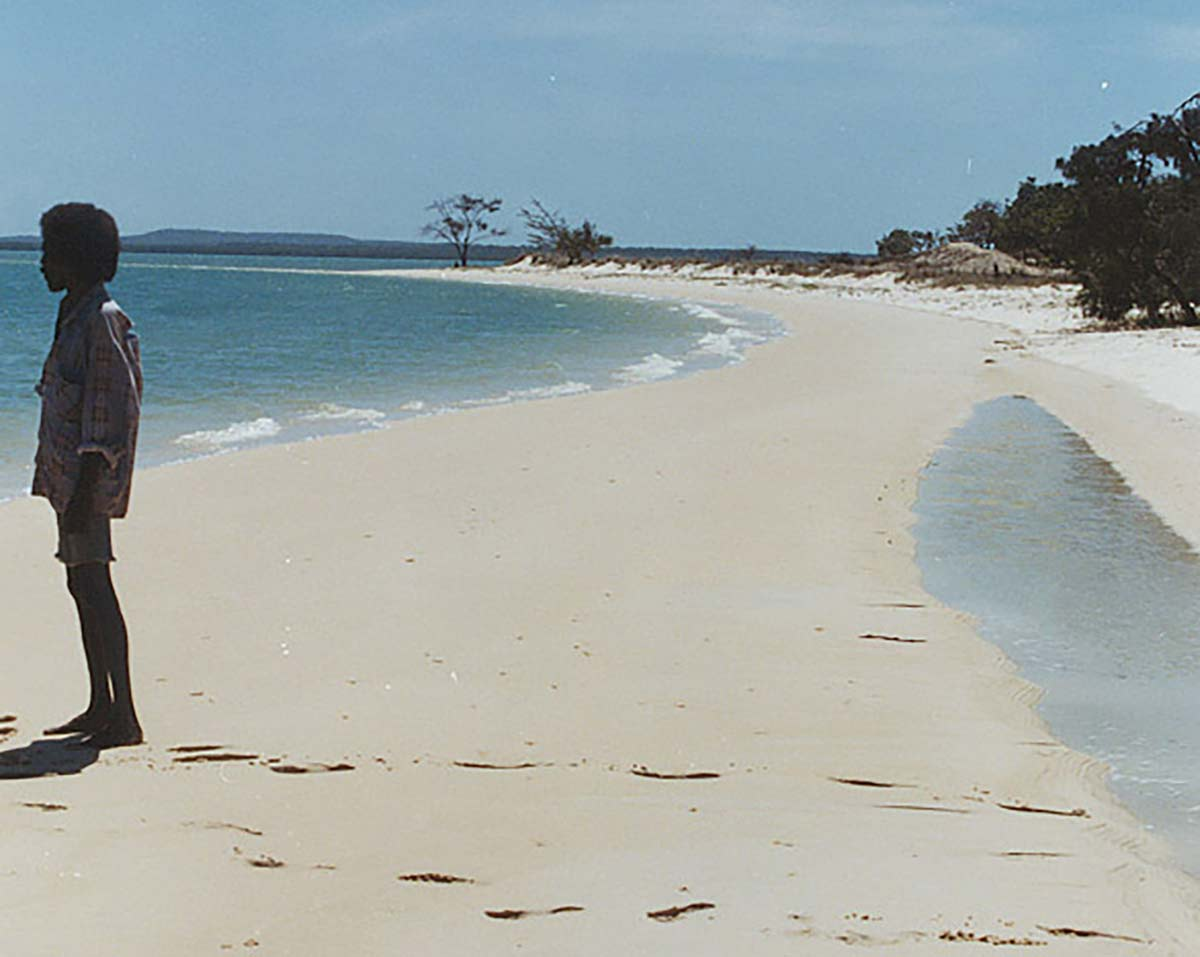 A colour photograph of a man standing on a beach. He stands to the extreme left of the image, looking out to sea. His footprints are behind him. The beach curves away into the distance. A few trees are partially visible at the right of the photograph. More coastline is just visible on the horizon. The sky above the horizon is blue and cloudless. - click to view larger image