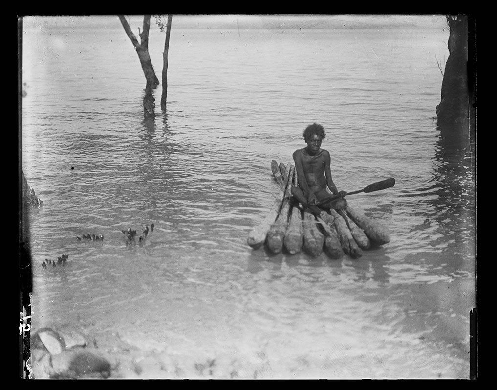 Black and white photograph of a young Australian Indigenous person seated on a raft and floating on a body of water. He is facing the camera and holding a paddle. The platform of the raft is made of eight logs tied together. Toward the rear of the raft, two other logs protrude diagonally from underneath the raft. - click to view larger image