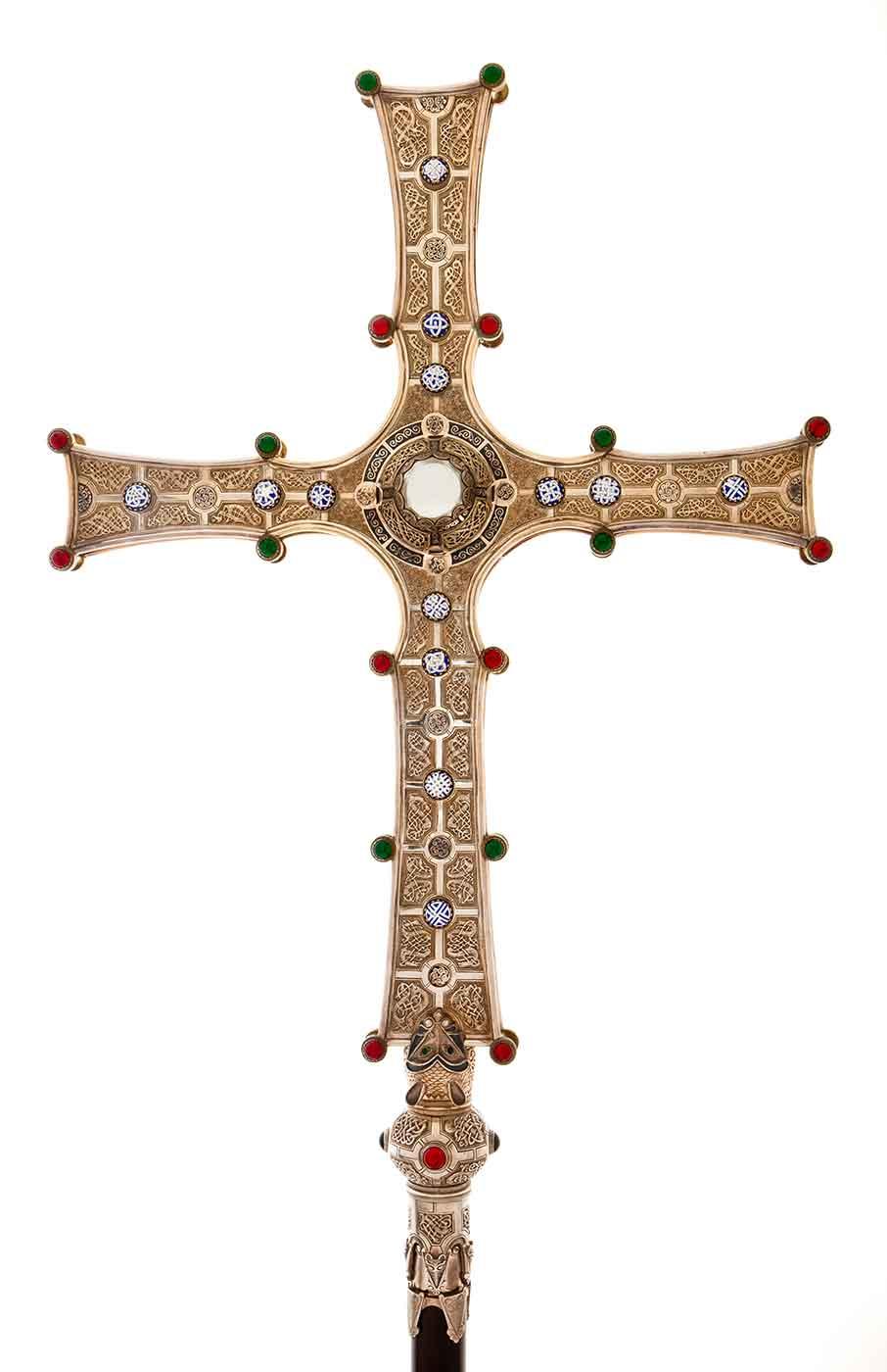 Golden cross with ornate Celtic design and gemstones.