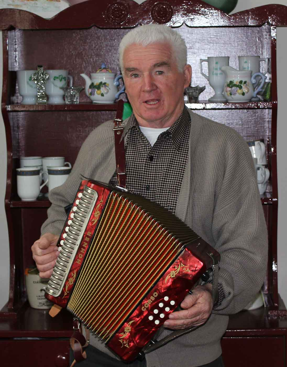 An elderly man is playing an accordion in front of a kitchen dresser. - click to view larger image