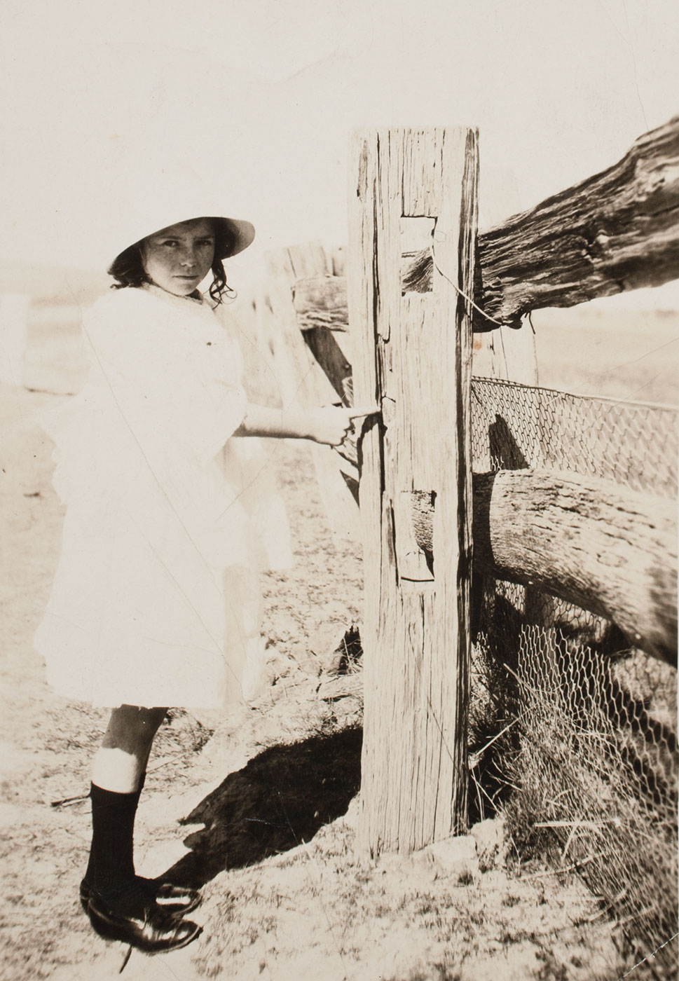 Black and white photo of a young girl standing adjacent to and pointing at an old wooden fence. - click to view larger image