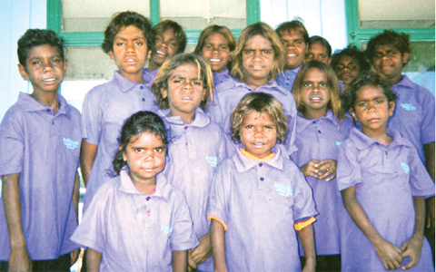 Fourteen children in lavender school uniform shirts face the camera.