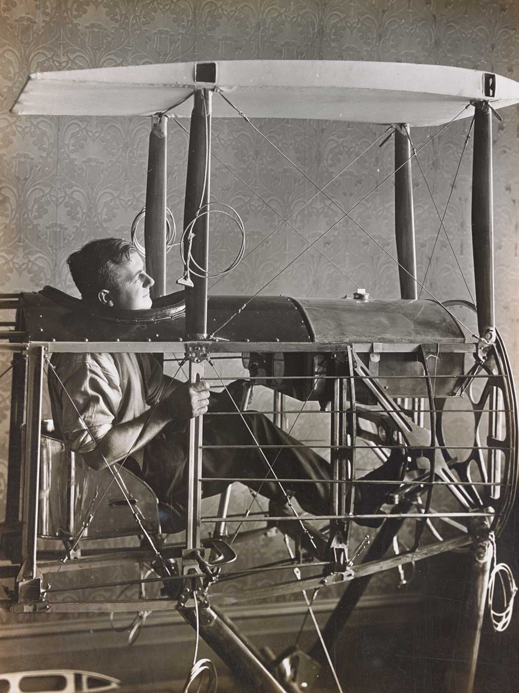 A man is sitting in a half-constructed aeroplane inside a room. - click to view larger image