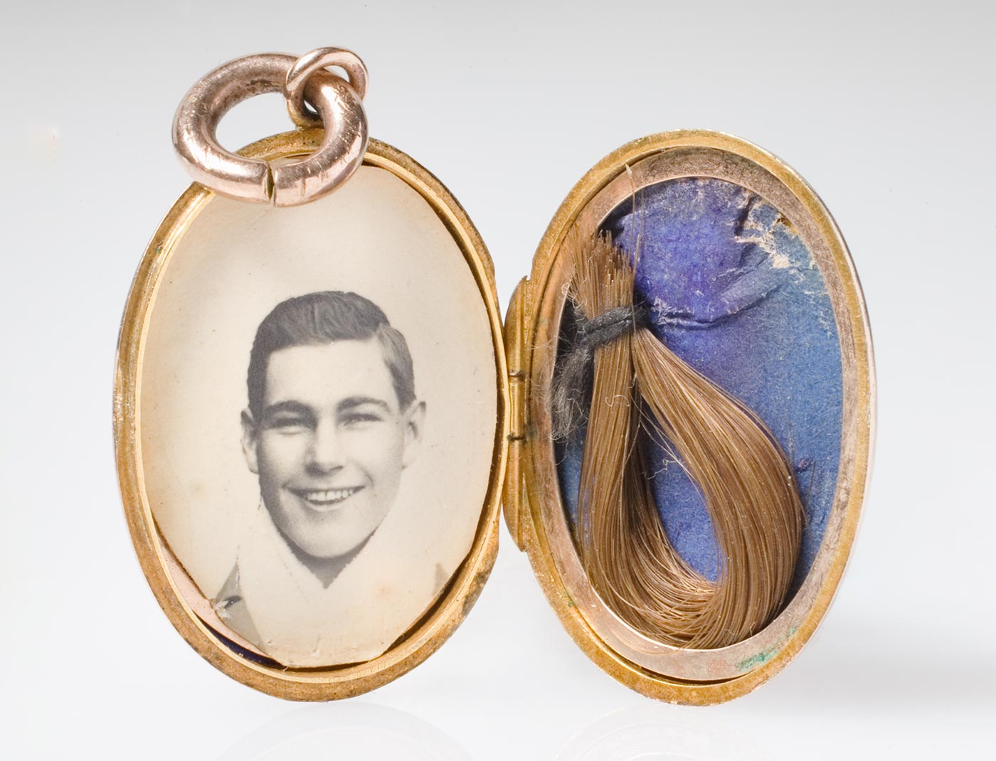 A locket containing a black and white photo of a smiling young man on one side and a lock of hair on the other.