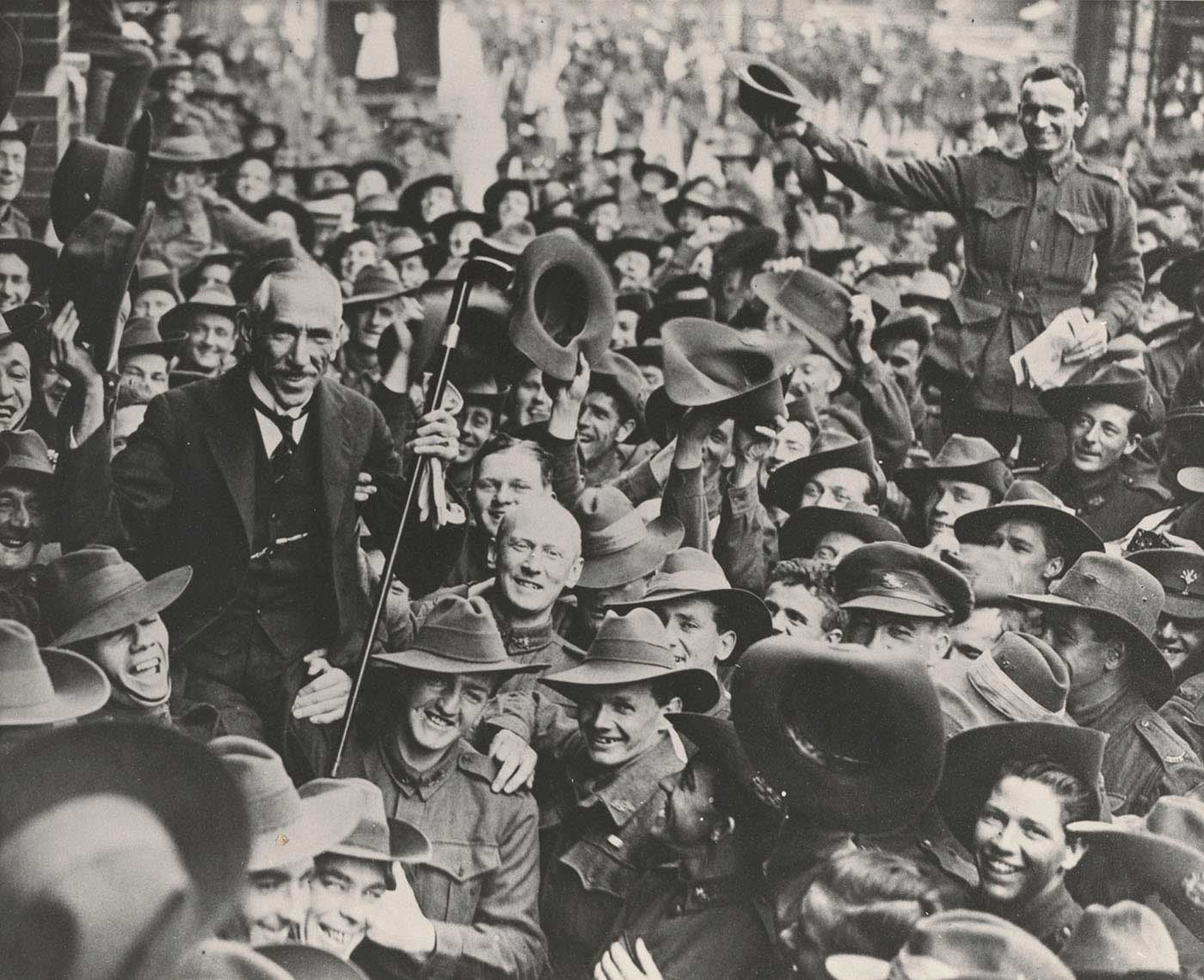 Black and white photo of a man being lifted up and celebrated by a large crowd of soldiers. - click to view larger image