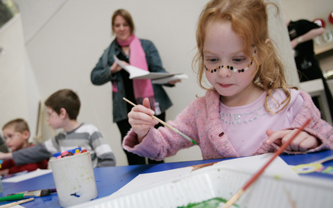 Three children at a table with crayons in a mug, paint brushes and paper. A girl, closest to the camera and on the right side of the image has dots painted across her face. An adult with additional paper is in the background, somewhat out of focus.