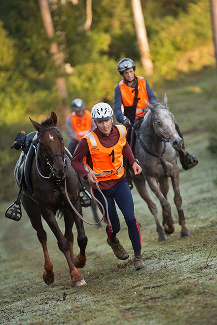 A man wearing a bright orange vest runs beside a horse. Two mounted riders follow. - click to view larger image