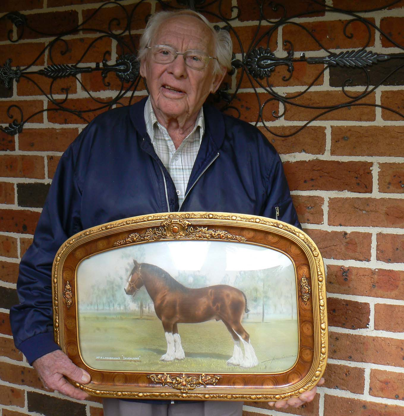 A man holds a framed portrait of a horse. - click to view larger image