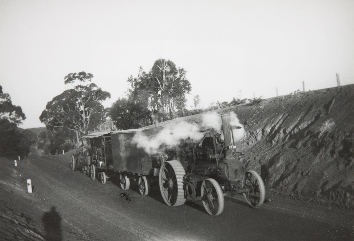 Steam-powered vehicle towing carriages on a dirt road. - click to view larger image